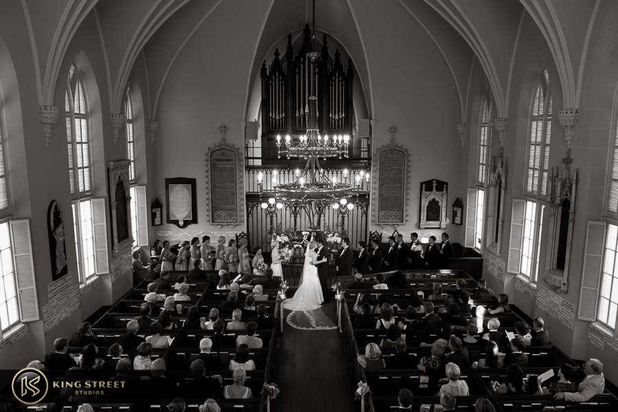 wedding pictures of bergen + philipe kissing at their ceremony by charleston wedding photographers king street studios